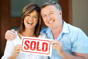 happy couple holding a real estate SOLD sign