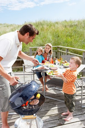 Photograph of a family barbecuing to illustrate fire safety while barbecuing.
