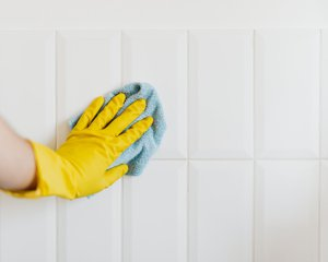 Gloved hand cleaning tile