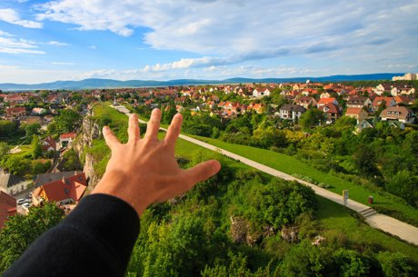 """Ariel photograph of a suburban neighborhood with an outstretched hand to illustrate, """"Top 5 Questions To Ask About Every Neighborhood""""."""