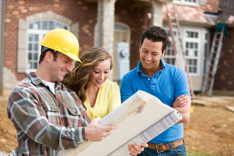 """Photograph of a couple reviewing blueprints with a builder to illustrate, """"To Buy An Existing Home Or Build A New One?""""."""