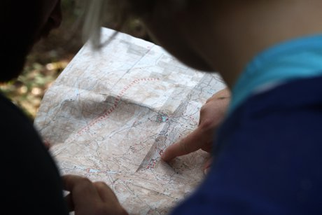 """Over the shoulder photograph of a couple looking at investment locations on a map to illustrate, """"The Best Locations To Invest In Real Estate""""."""
