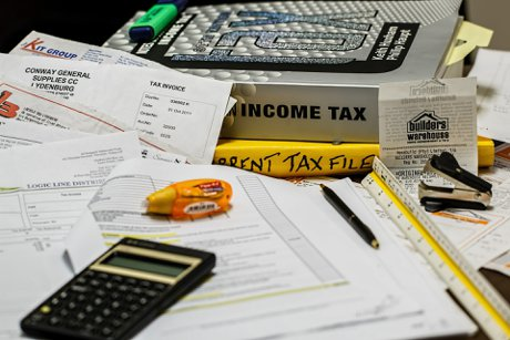 """Photograph of income tax related paperwork on a desk to illustrate, """"Some Real Estate Tax Ramifications""""."""