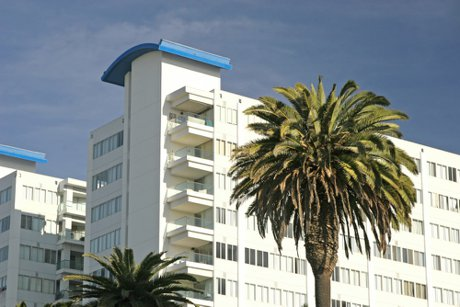 """Photograph of an apartment building or condo development in a tropical locale to illustrate, """"3 Benefits Of Buying A Condo""""."""