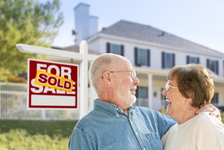 """Photograph of a Happy Affectionate Senior Couple Hugging in Front of Sold Real Estate Sign and House to illustrate, """"Why It's Never Too Late To Buy A House""""."""