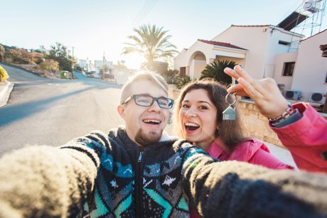 """Photograph of a happy smiling young couple showing a keys of their new house to illustrate, """"5 Reasons To Buy A Home While You're Young""""."""