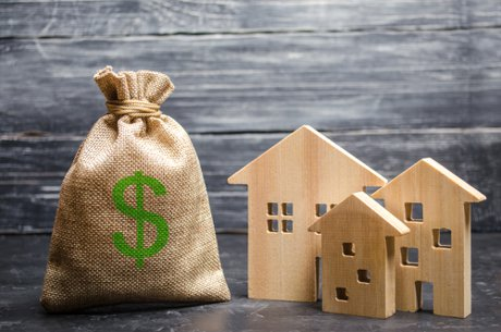 """Photograph of a bag with money and three wooden houses to illustrate, """"How Real Estate Investors Progress Naturally""""."""