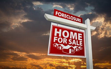 """Red Foreclosure Home For Sale Real Estate Sign Over Beautiful Clouds and Sunset Sky to illustrate, """"5 Pros & 3 Cons Of Investing in Foreclosure & Pre-Foreclosure Properties""""."""
