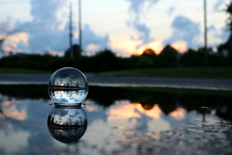 """Photograph of a crystal ball with a suburban background to illustrate, """"Fine-tuning Your Commercial Real Estate Crystal Ball""""."""
