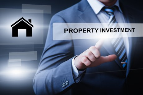 """Man in suit pointing at property investment sign to illustrate, """"The Effects Of The Coronavirus On Real Estate Investing"""""""