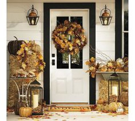 front porch decorated with pumpkins, lanterns, & fall leaf wreath