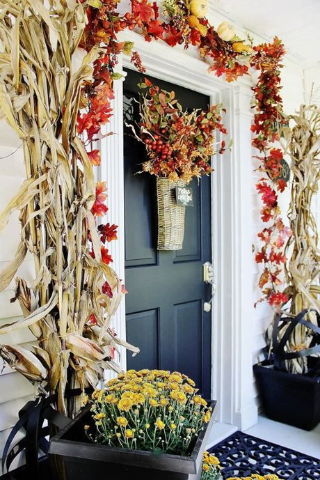 front porch decorated with corn stalks, red & orange leaves, and a fall basket