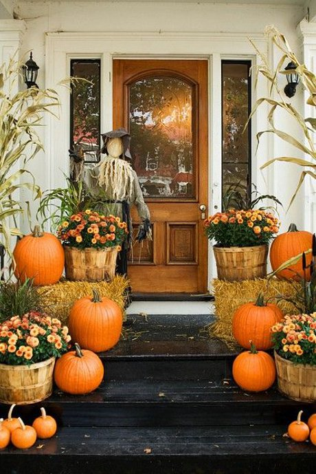 front porch decorated with pumpkins, flowers, and a scarecrow