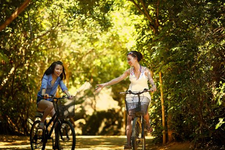 Two girls riding bicycles in a park.