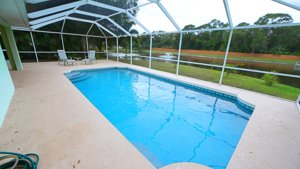 The expansive pool area overlooks a quiet lake